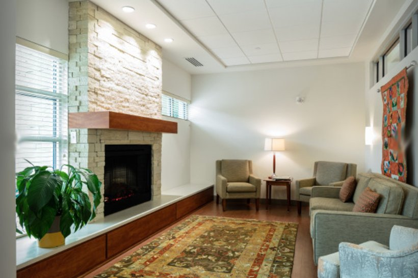 NC Hospice House family meeting area with fireplace and beautiful furniture, lighting and windows