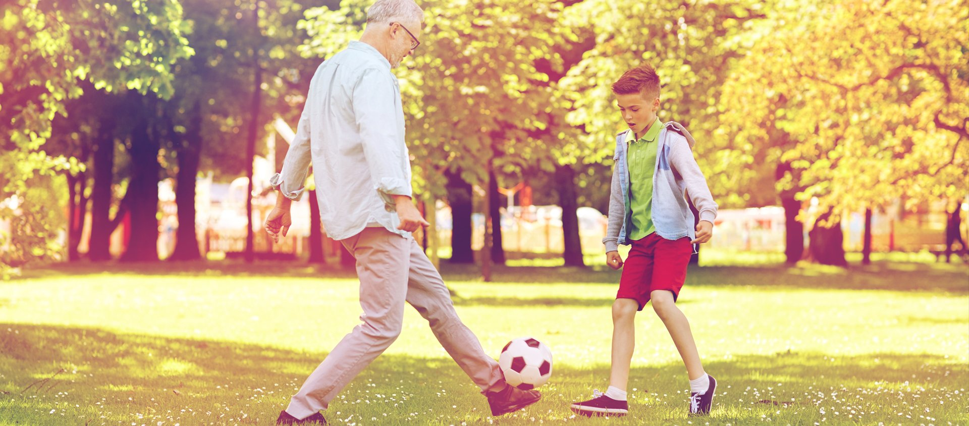grandfather playing soccer with grandson